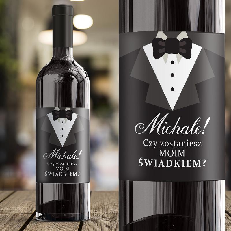 Etykieta na wino z garniturem na którym jest biały napis Czy zostaniesz moim świadkiem, Etkieta jest na butelce wina. Widok z bliska oraz przybliżenie.