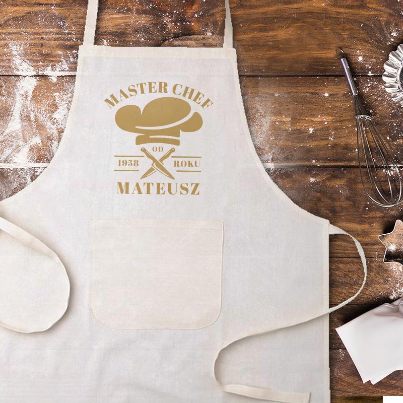 Biały fartuch z żółtym napisem na przedzie master szef + imię oraz data. Obok napisu jest także rysunek czapki kucharskiej oraz dwóch skrzyżowanych noży.