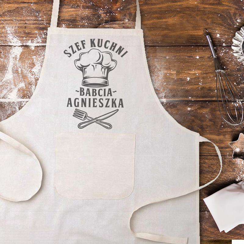 Biały fartuch kuchenny z wiązaniem z tyłu i nadrukiem. Na przedzie fartucha jest napis Szef kuchni z imieniem oraz czapka kucharska i skrzyżowane nóż i widelec. Fartuch leży na drewnianym blacie, uprruszonym mąką.