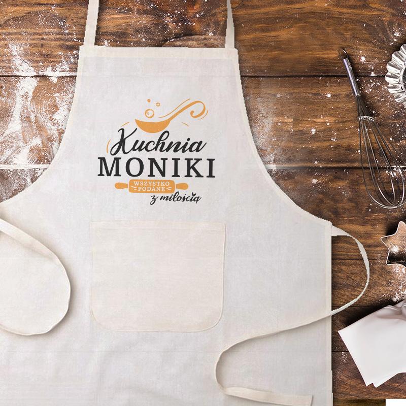 Biały fartuch kuchenny z napisem Kuchnia + imię wszystko zrobione z miłością. Napisy znajdują się na środku fartucha. Jest wiązany z tyłu i ma na przedzie małą kieszonkę.