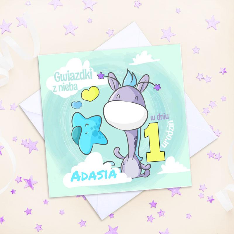 Niebieska kartka kwadratowa z fioletową żyrafą która trzyma niebieską gwiazdkę. Na kartce są też życzenia i imię dziecka