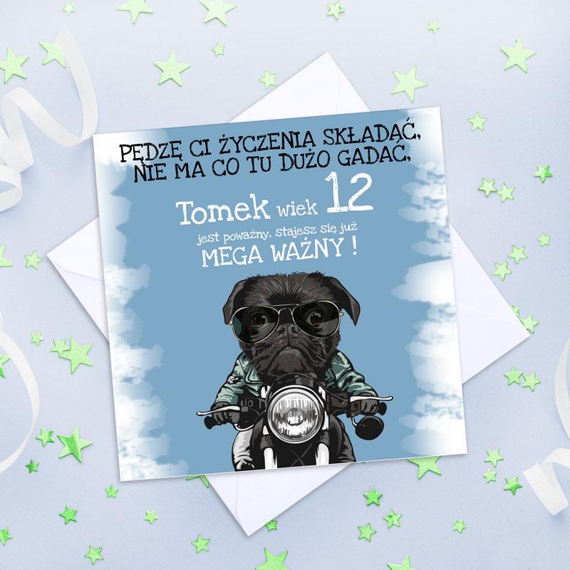 Niebieska kwadratowa kartka z czarnym psem, który jedzie na motorze. Na górze jest biało-czarny napis skierowany do solenizanta. Kartka leży na białej kopercie.