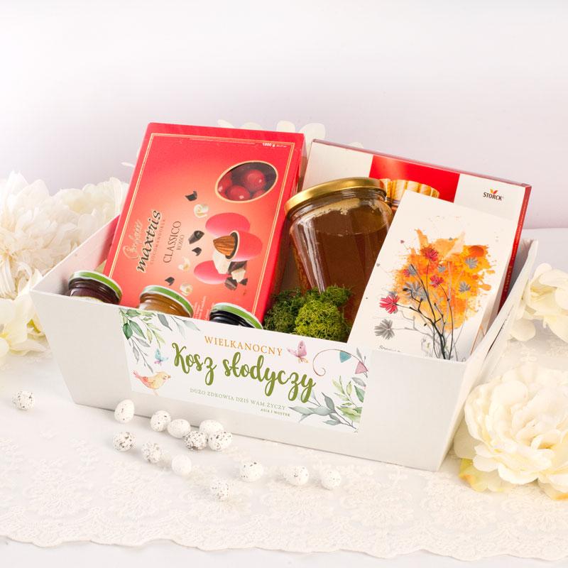 Biały kosz z bilecikiem z życzeniami Wielkanocnymi. W środku są czekoladki, migdały, miód, herbata, dżemiki
