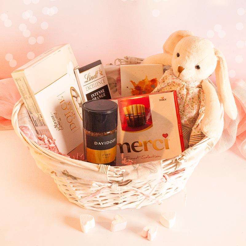 Kosz wiklinowy z prezentami: pluszowy królik, kawa, czekolada, czekoladki, migdały i herbata