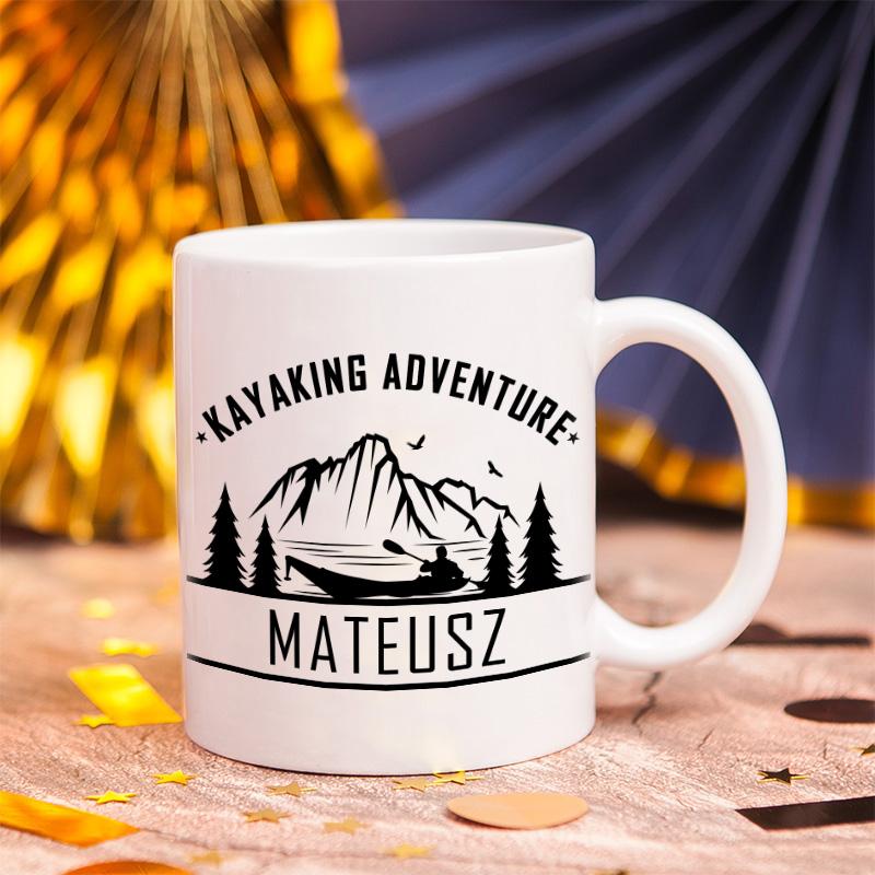 Biały ceramiczny kubek z czarnym rysunkiem wiosłującego kajakarza na tle gór i lasów. Obok obrazka są napisy imię oraz tytuł kayaking adwenture.