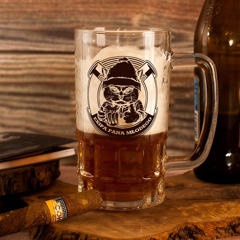 Szklany kufel na piwo z tematycznym białym nadrukiem Ekipa Pana Młodego. Napis dopełnia rysunek kota, który trzyma w łapie kufel z piwem.