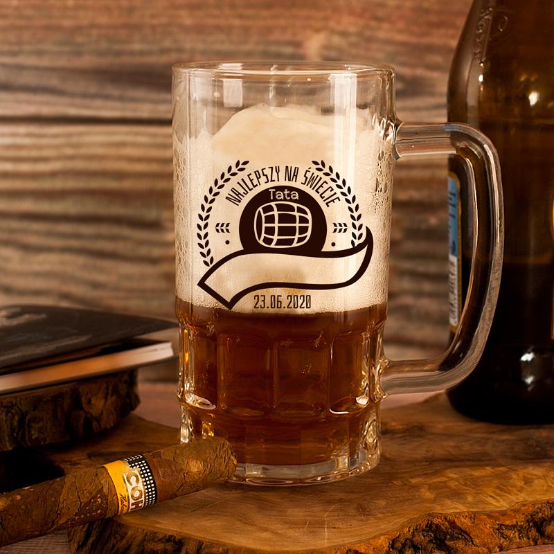Kufel szklany wysoki na piwo z czarnym napisem Najlepszy na świecie tata z miejscem na szarfie żeby dodać tam imię. Napis jest w dekoracyjnym wianku.