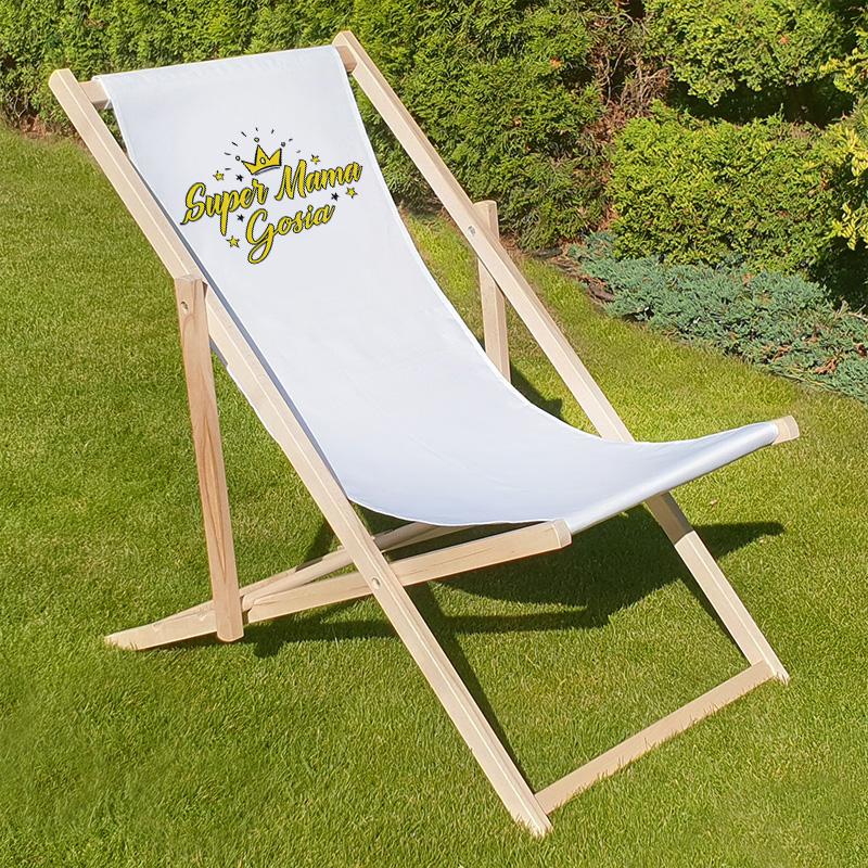 Leżak z drewnianym stelażem i białym poszyciem na którym jest żółty napis Super mama z imieniem. Leżak stoi w ogrodzie na trawie.