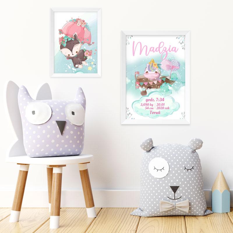 Metryczka na plakacie z lecącym w samolocie jednorożcem oraz obrazek z leśnym misiem. Dwa plakaty na białej ścianie, a obok stoją maskotki w szarym kolorze, jedna siedzi na drewnianym stołku.