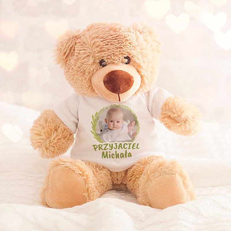 Pluszowy miś w białek koszulce na której jest zdjęcie dziecka i napis przyjaciel z imieniem. Zdjęcie jest w zielonym wianuszku, litery są też zielone.