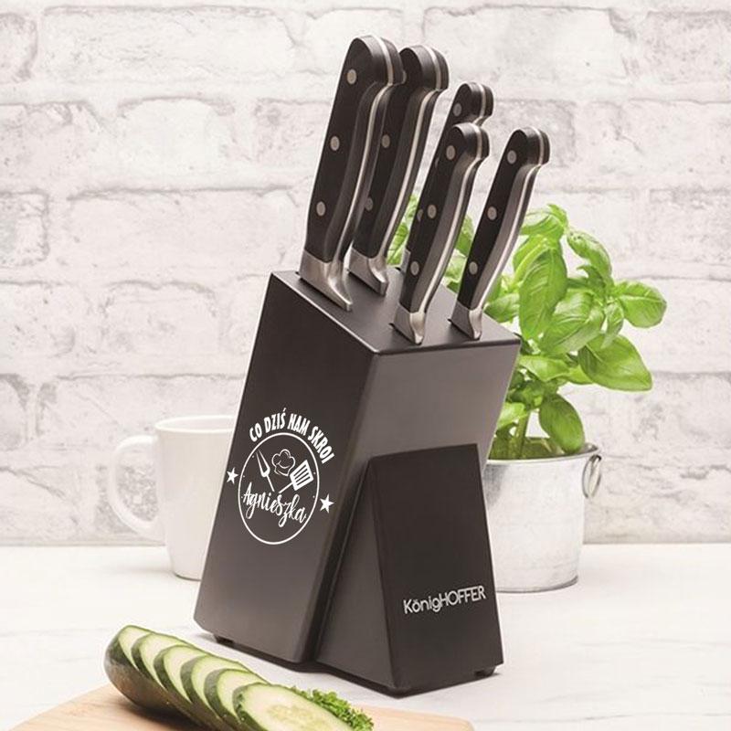 Noże w czarnym stojaku na którym jest napis Co nam dziś skroi ... z imieniem. Stojak jest w kuchni na białym blacie. Rączki noży są też czarne.