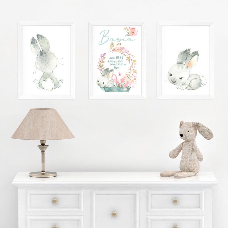 Zestaw plakatow, które wiszą na białej ścianie. Trzy plakaty w białych ramkach z królikiem. Na środkowym jest metryczka dziecka i imię. Plakaty wiszą nad białą komodą, na której stoją lamka nocna i pluszowy miś.