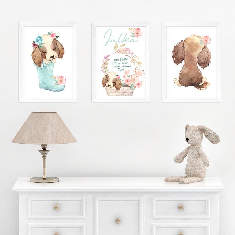 Trzy plakaty na białej ścianie. W środku jest plakat z metryczką a obok piesek w kaloszu a drugi obrazek przedstawia odwróconego pieska. Plakaty wiszą na białej ścianie i nad komodą.