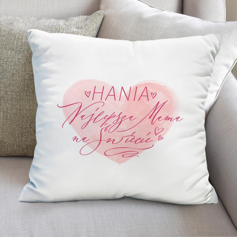 Miękka poduszka w białej poszewce z nadrukiem. Na tle czerwonego, pastelowego serca jest napis najlepsza mama na świecie z iniem. Poduszka leży na szarej sofie..