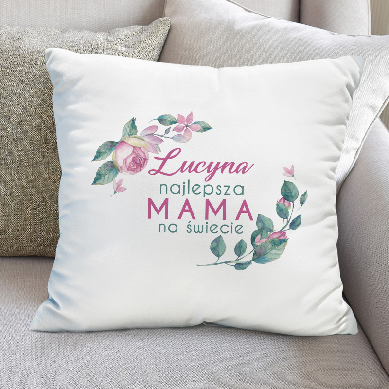 Biała poduszka z nadrukiem na poszewce, w postaci kwitaów róży i napisem Najlepsza mama na świecie.