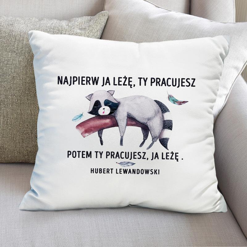 Biała poduszka z kolorowym nadrukiem w postaci śpiacego na gałęzi szopa oraz zabawnym napisem Najpier ja leżę ty pracujesz, potem ty pracujesz ja leżę.