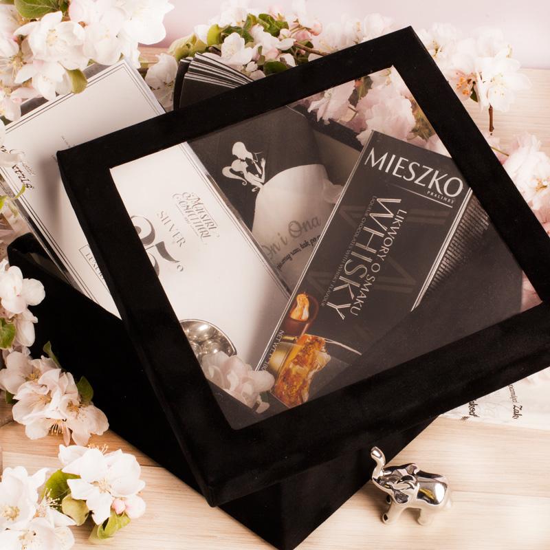 Welurowe pudełko ze srebrnymi migdałami, likworami, serwetkami i srebrnym słonikiem w środku. Pudełko ma na wieczku szybkę, przez którą widać wypełnienie pudła.
