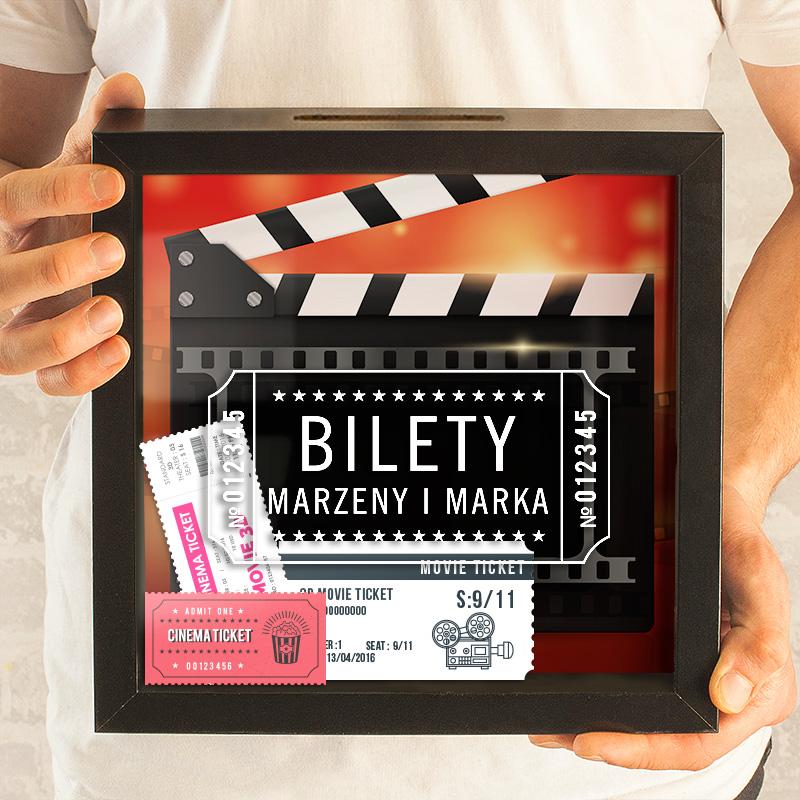 Czarna Ramka skarbonka z szybką na bilety do kina. Na szybce jest personalizowany nadruk z tytułem Bilety oraz imionami kolekcjonerów.