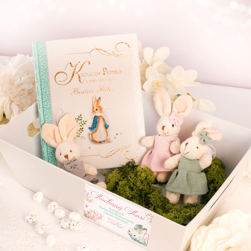Biała skrzynka, a w środku na zielonym mchu leży ksiązka dla dzieci i trzy maskotki króliczki w ubrankach. Na ściance skrzynki jest bilecik z dedykacją na Wielkanoc.