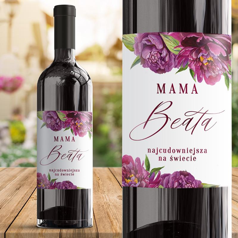 Wino z etykieta dla mamy z napisem mama najcudowniejsza na świecie z imieniem. Wokół napisu na górze i dole etykiety są fioletowe piwonie. Widok butelki z etykietą dla mamy z bliska i z daleka.