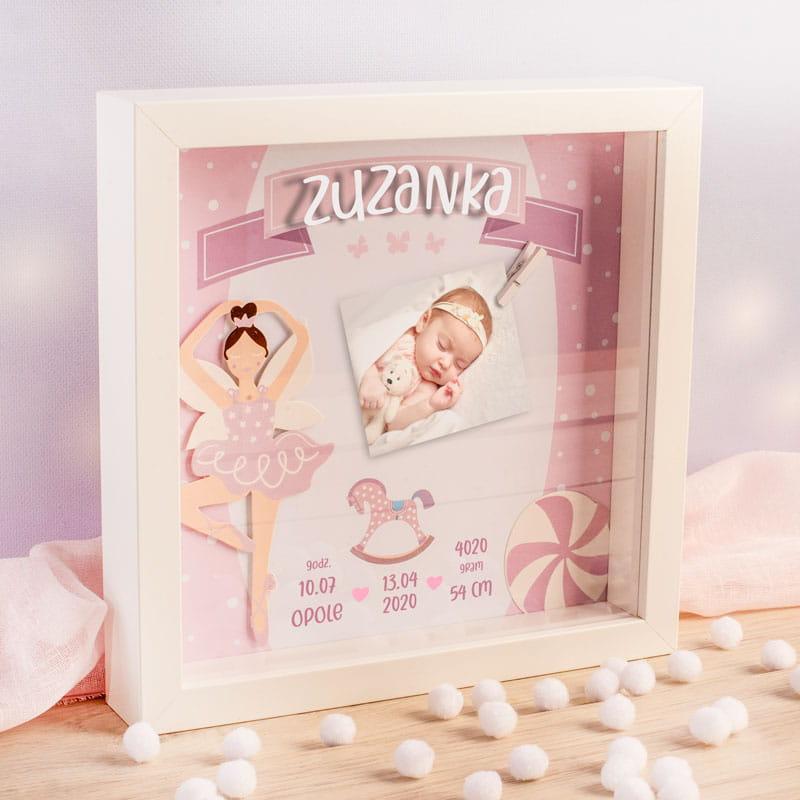 Biała ramka z szybką na której jest imię dziewczynki. Za szybką jest grafika z metryczką dziecka, zdjęciem i rysunkami baletnicy i konika na biegunach.