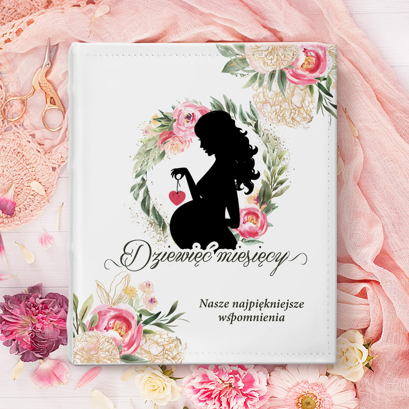 Album na zdjęcia z imieniem przyszłej mamy i grafika ciężarnej kobiety w kwiatowym wianku.