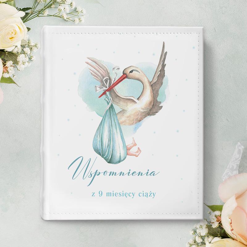 Album na zdjęcia z okładką z eko skóry z motywem bociana z błękitnym becikiem. Na okładce jest miejsce na imię kobiety w ciąży.