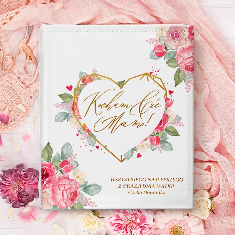 Album na zdjęcia z napisem w sercu kocham Cię mamo oraz z podpisem i życzeniami. Na okładce znajdują się też kwiaty.