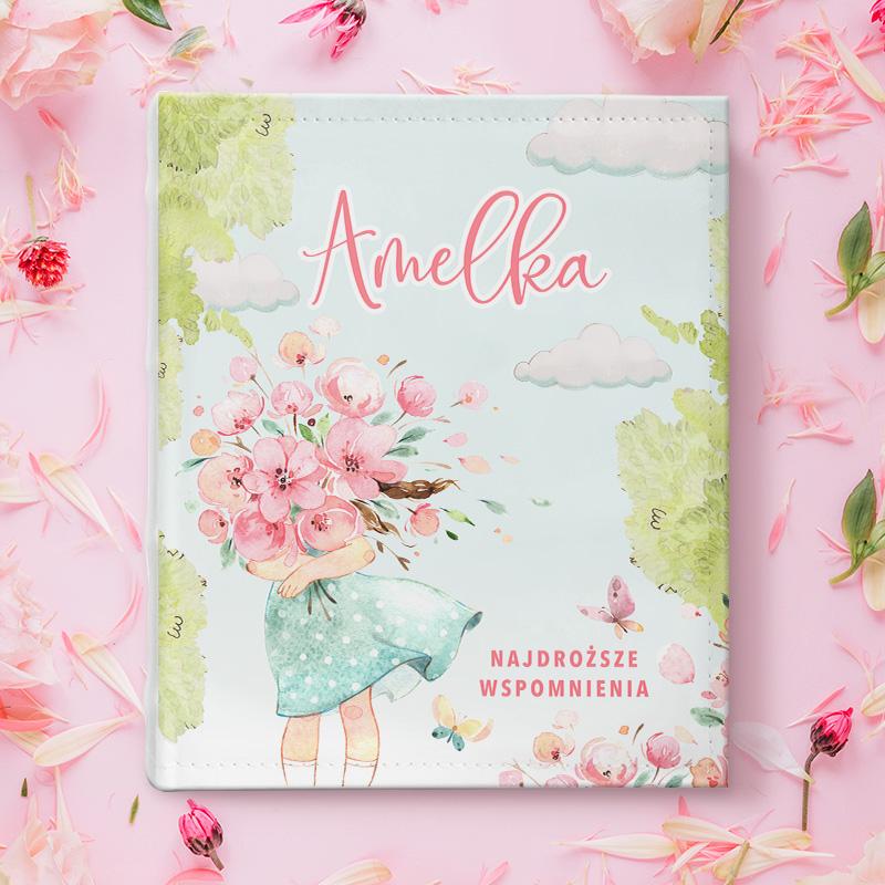 Album na zdjęcia w pastelowych kolorach przedstawiający dziewczynkę z ogromnym bukietem różowych kwiatów na tle błękitnego nieba z chmurkami z personalizowanym napisem