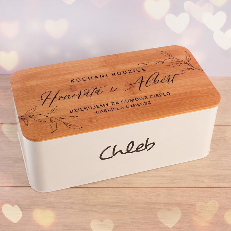 Personalizowany chlebak z grawerem na pokrywie, który jest podziękowaniem ślubnym dla rodziców. Drewniana pokrywa to także deska do krojenia. Prezent ślubny
