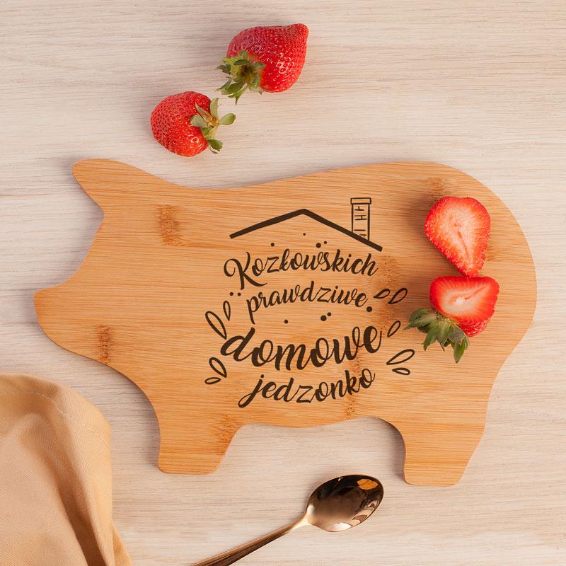 Drewniana deska w kształcie świnki na której znajduje się nadruk z nazwiskiem rodziny i ozdobnikiem, który wygląda jak domek.