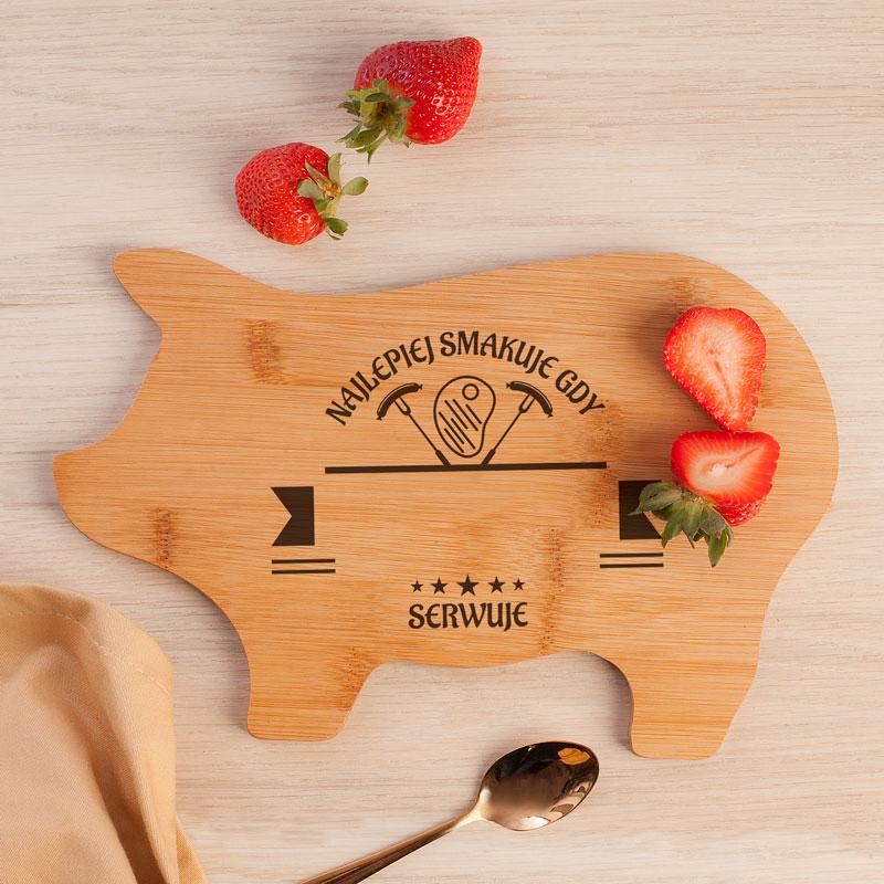 Deska drewniana w kształcie świnki, która ma napisy dekoracyjne najlepiej smakuje gdy .... + imię ... gotuje.
