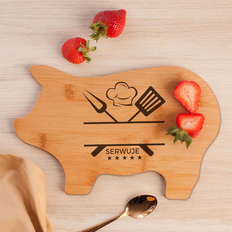 Deska drewniana w kształcie świnki z miejscem na uzupełnienie imienia i oraz motywem narzędzi kuchennych.