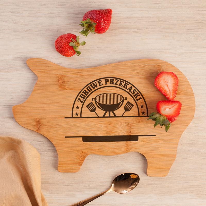 Drewniana deska w kształcie świnki z nadrukiem na płaskiej powierzchni oraz z miejscem na podpis.