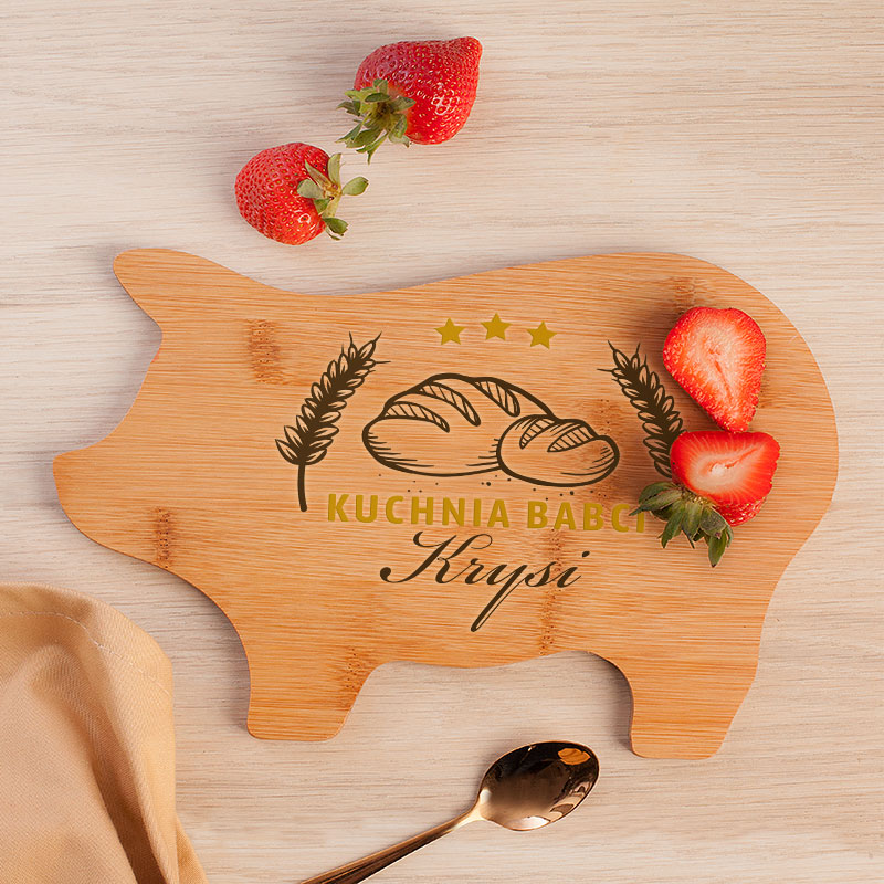 Deska kuchenna w kształcie świnki z napisem kuchnia babci oraz miejscem na imię babci. Na desce jest grafika z chlebem i na niej leżą soczyste truskawki.