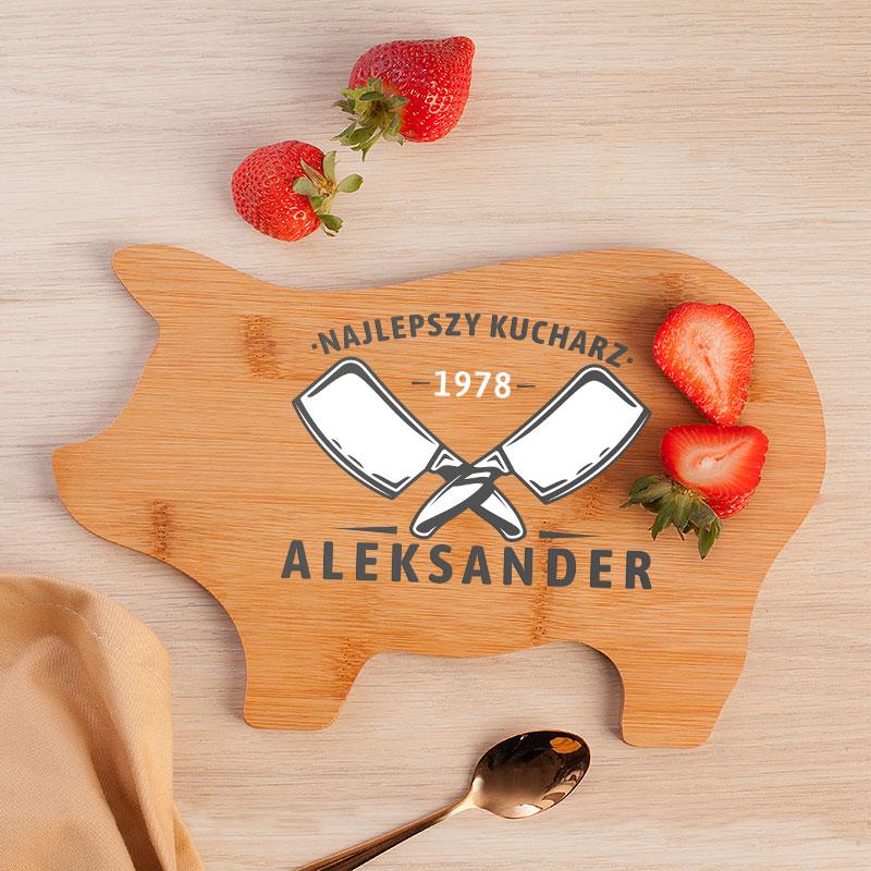 Drewniana deska w kształcie świnki z nadrukiem najlepszy kucharz i obrazkiem dwóch skrzyżowanych tasaków. Na desce leżą soczyste truskawki.