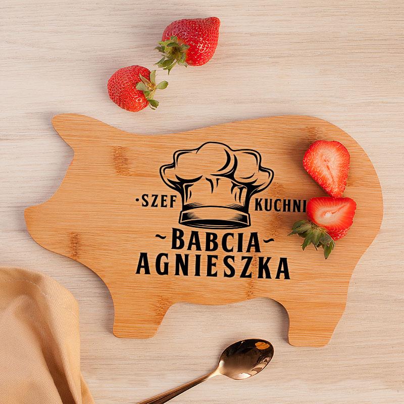 Deska w kształcie świnki zrobiona z drewna i napisem szef kuchni oraz czapką kucharską.