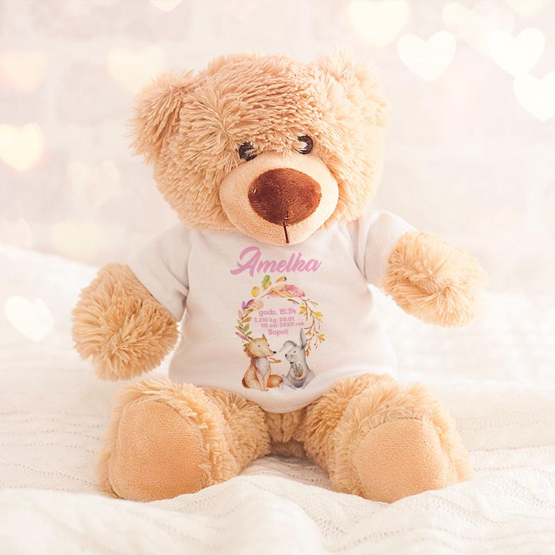 Miś pluszowy z koszulką na której znajdują się lisek oraz zajączek, a także imię dziecka oraz jego metryczka.