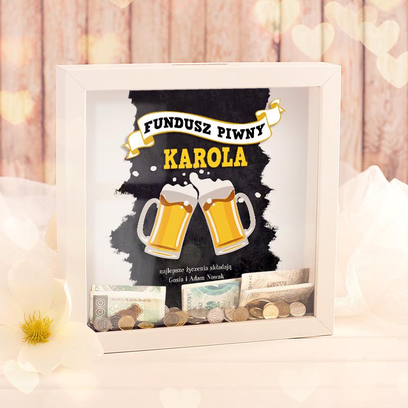 Skarbonka 3D w czarnej ramce z dwoma kuflami z piwem oraz dedykacją na białej szarfie Fundusz piwny + imię oraz podpis.