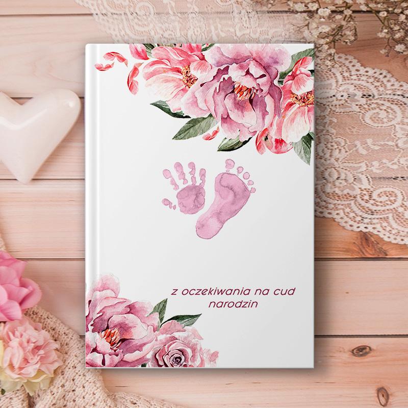 Notatnik personalizowany z imieniem ciężarnej i motywem różowych odcisków dłoni i stóp oraz dekoracji kwiatowych.