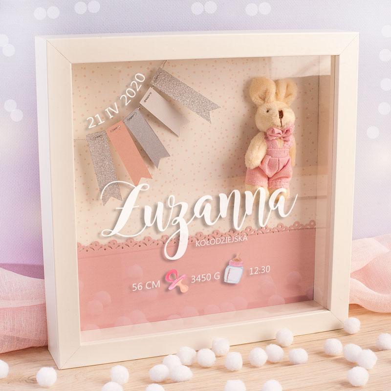 Biała ramka z szybką na której znajduje się imię dziecka, nazwisko oraz dane z metryczki. Wewnątrz ramki umieszczony jest na tle różowej dekoracyjnej kartki króliczek w różowych spodniach z muchą. Po drugiej stronie wisi mały baner z kolorowymi paskami.