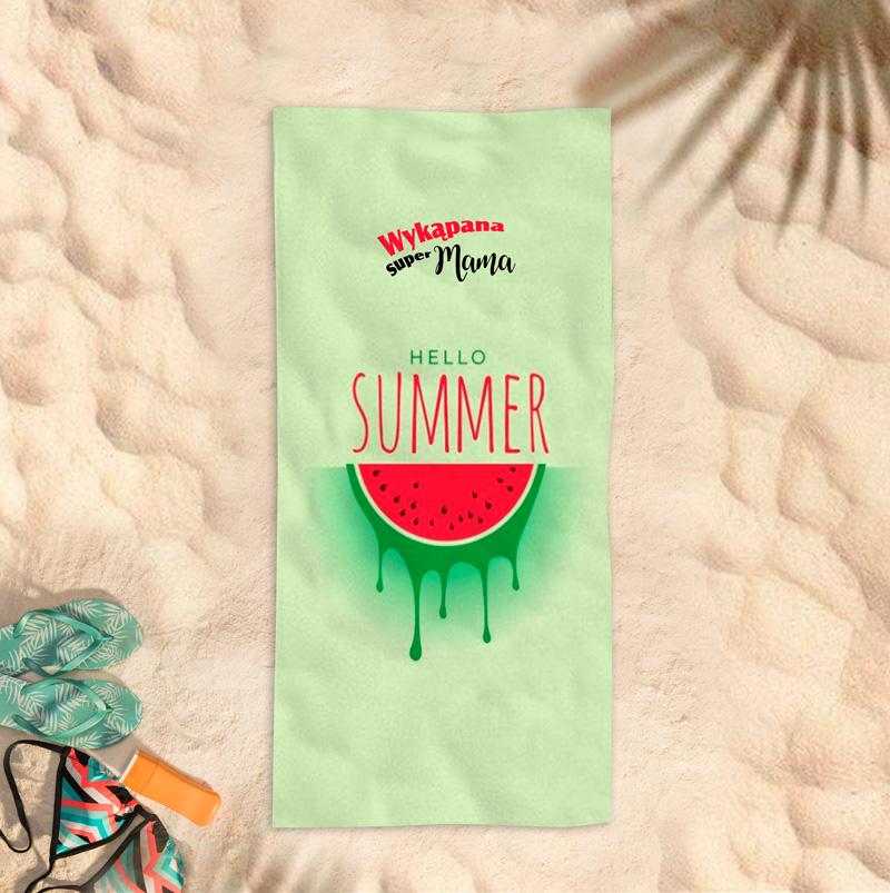 Wakacyjny ręcznik na plażę w zielonym kolorze z motywem arbuza, czerwonym napisem hello summer oraz dedykacją dla mamy z miejscem na jej imię. Ręcznik jest prostokątny i leży na piaszczystej plaży.