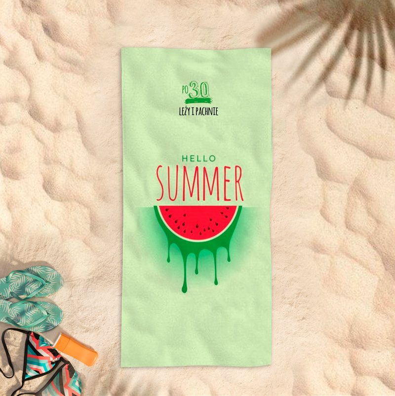 Ręcznik plażowy z nadrukiem w arbuza, dedykacją na 30 urodziny dla kobiety oraz miejscem na jej imię. Ręcznik leży na piaszczystej plaży.