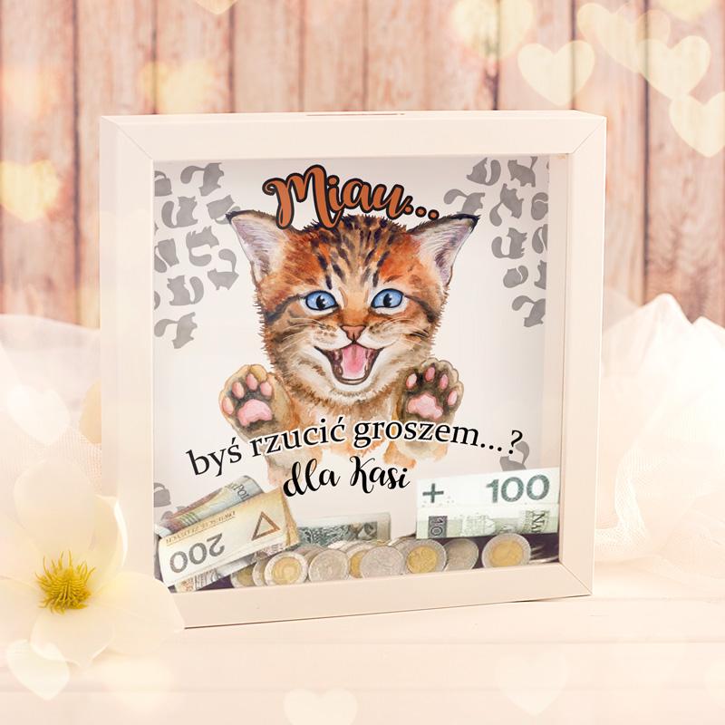 Personalizowana skarbonka 3D w białej ramce z dekoracyjnym obrazkiem w środku - małym kotkiem. Na szybce skarbonki jest napis miau być grosz dla + imię.
