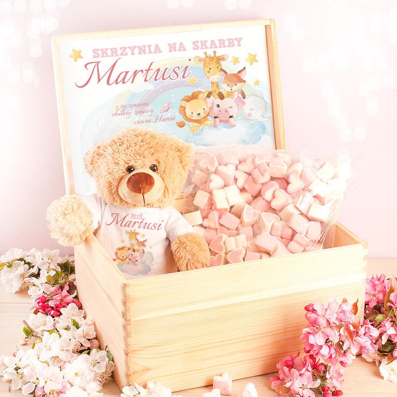 Drewniana skrzynka z dekoracyjnym wieczkiem z życzeniami dla dziecka, W środku znajduje się pluszowy miś w koszulce z imieniem dziecka a takze wielka paczka słodkich pianek do jedzenia w kształcie serduszek.