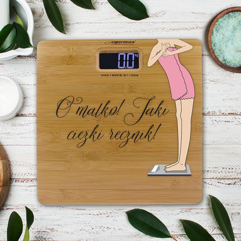 Waga łazienkowa bambusowa z kobietą, która waży się w ręczniku. Obok jest napis jaki ciężki ręcznik. Do dekoracji dodamy Twoją dedykację, która będzie wydrukowana bezpośrednio na wadze.