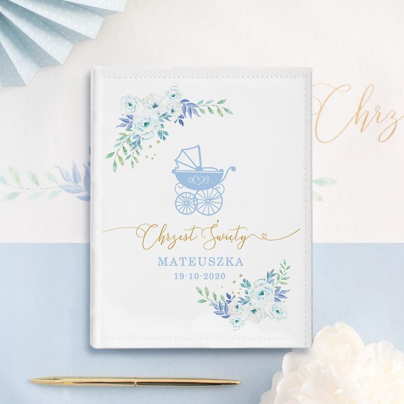 Album na zdjęcia jako pamiątka chrztu. Dziecięca grafika niebieski wózek w otoczeniu delikatnych kwiatków, z imieniem dziecka i datą chrztu