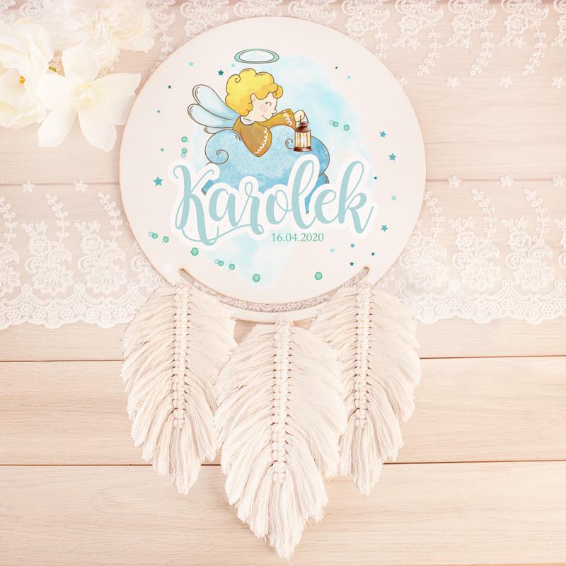 Łapacz snów z trzema ręcznie plecionymi piórkami i kolorowym nadrukiem na okrągłej tarczy łapacza. Znajduje się tam wizerunek słodkiego aniołka z jasnymi włosami oraz imię dziecka i data narodzin.