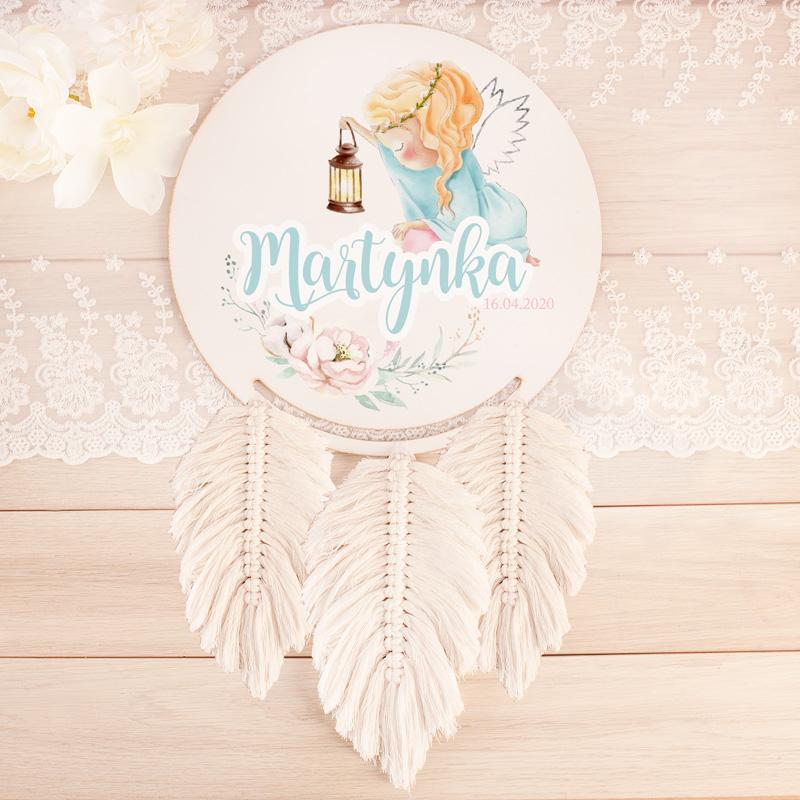 Drewniany łapacz snów z ręcznie plecionymi, jasnymi piórkami i nadrukiem na tarczy. Na łapaczu znajduje się obrazek aniołka dziewczynki, imię dziecka oraz datę narodzin.