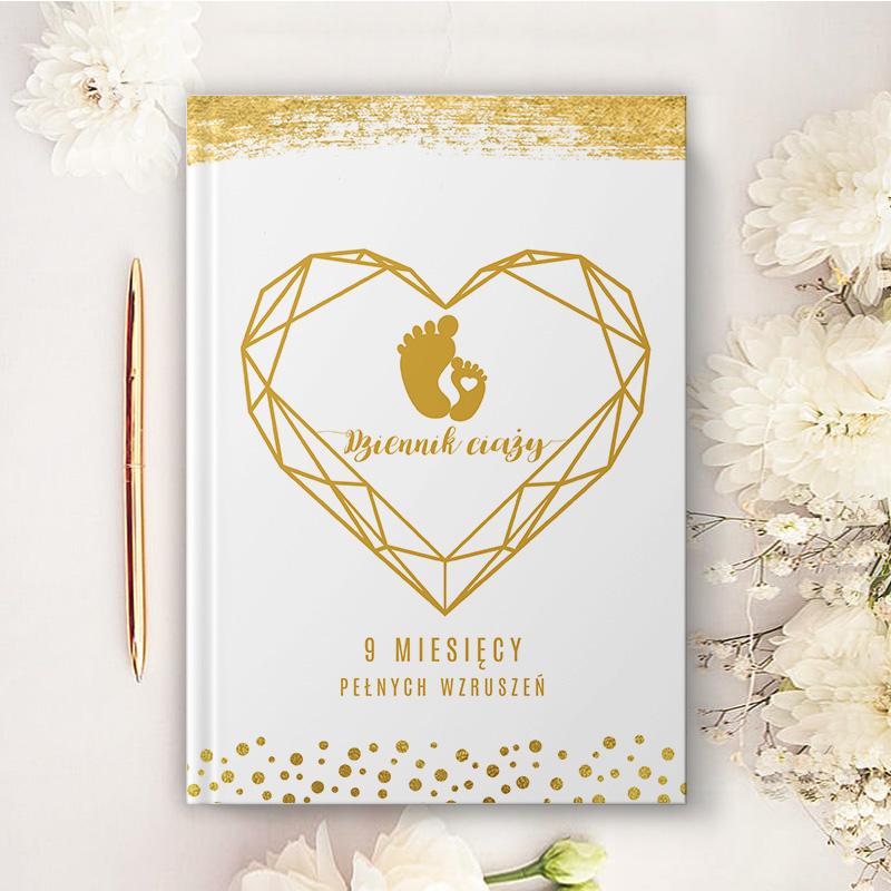 Personalizowany notatnik o ciąży z dekoracyjną grafiką i miejscem na uzupełnienie imienia. W środku złotego, geometrycznego serca znajduje się motyw stópek oraz miejsce na imię mamy.